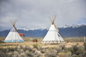 teepees on the plains in front of snowy mountains